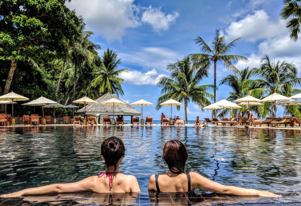 two woman leaning on inground pool tile