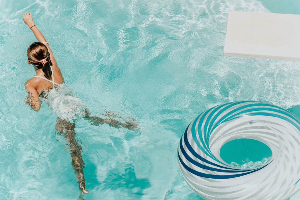 girl swimming in pool with inner tube