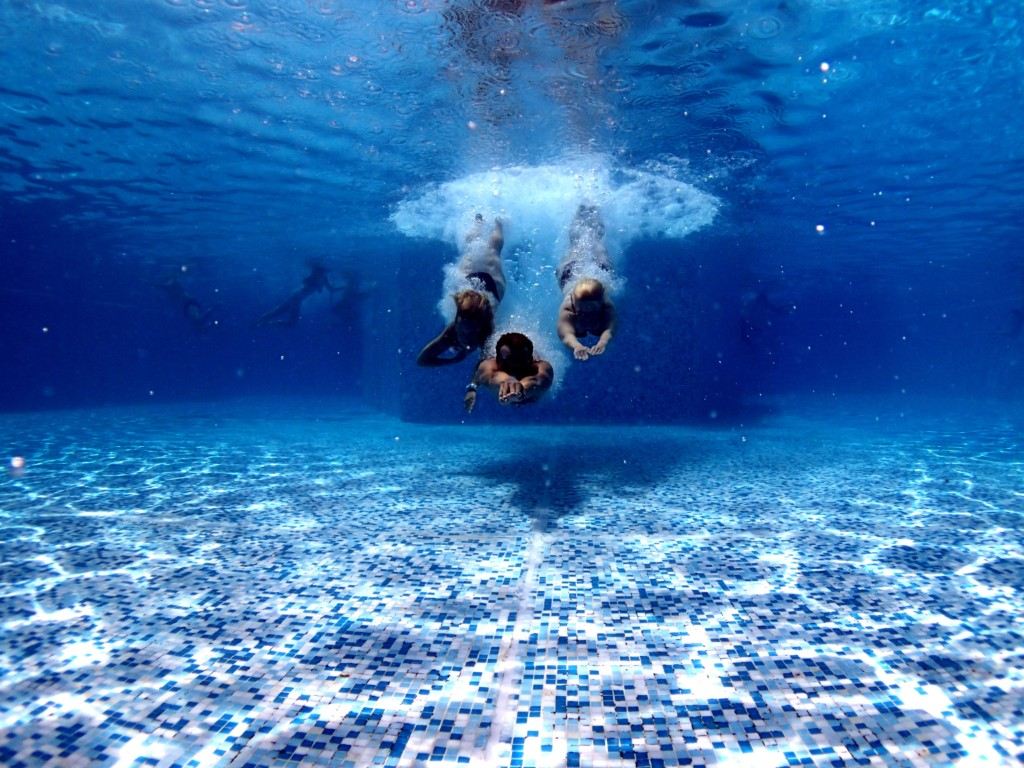 three people diving into water pool