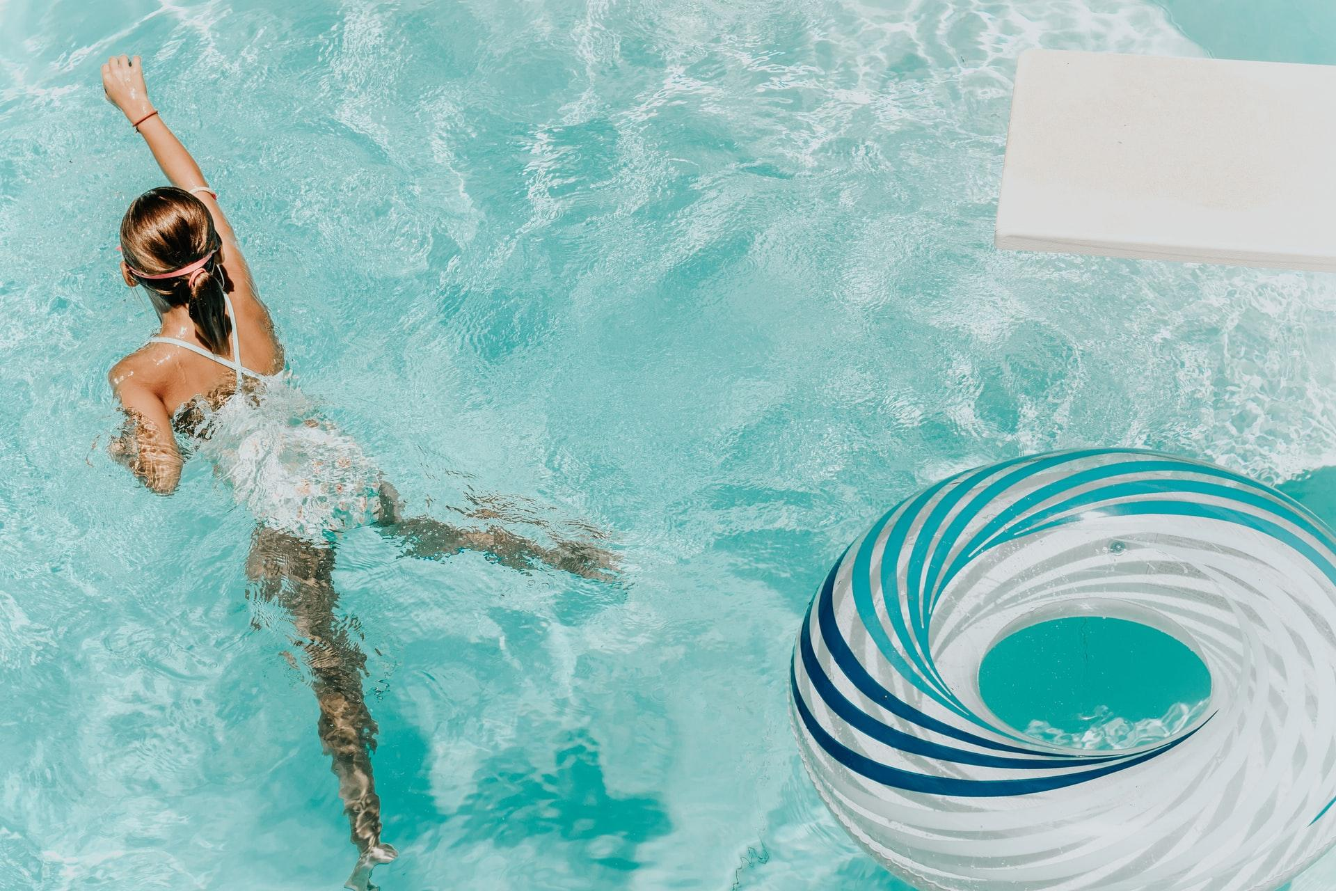 girl wearing swimsuit and swims in swimming pool