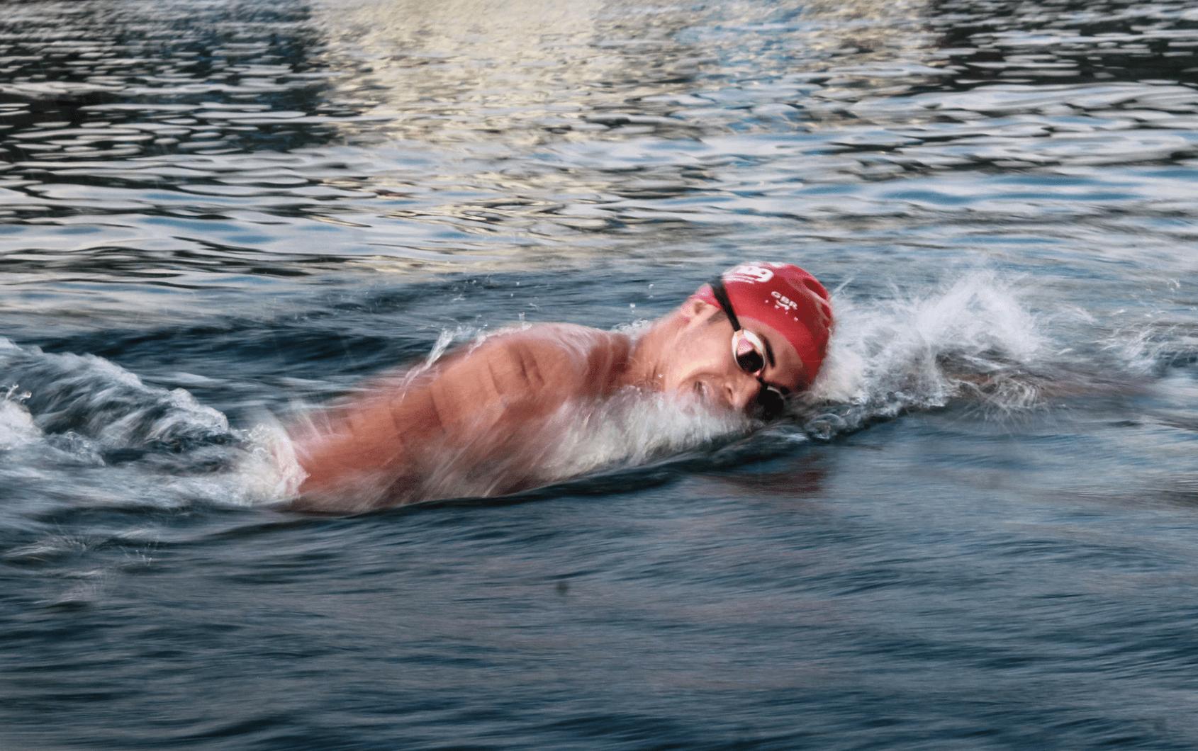 man swimming on body of water during daytime