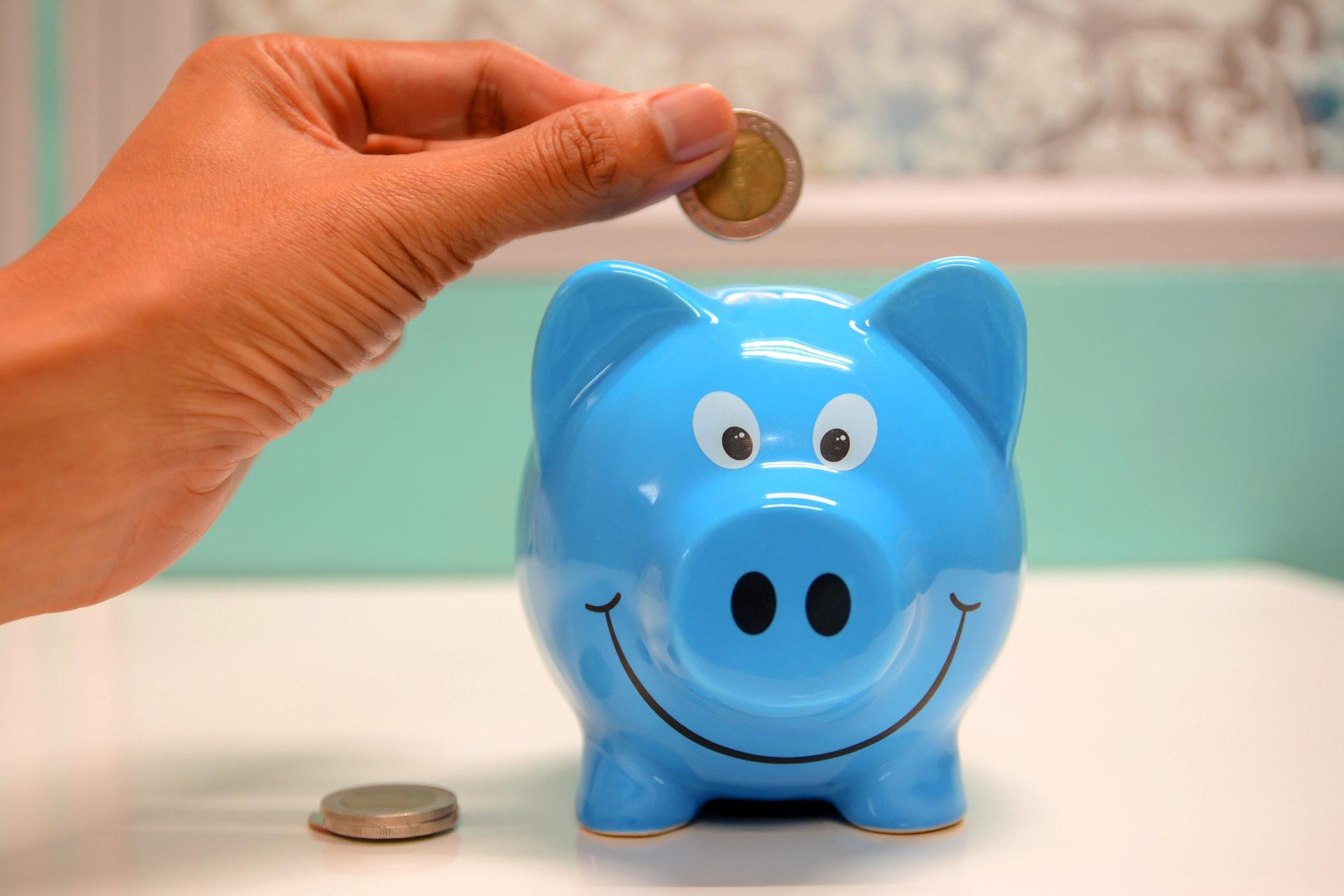 person holding coin in piggy bank