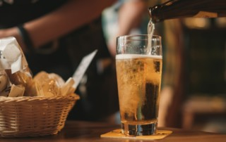 beer being poured into glass cup