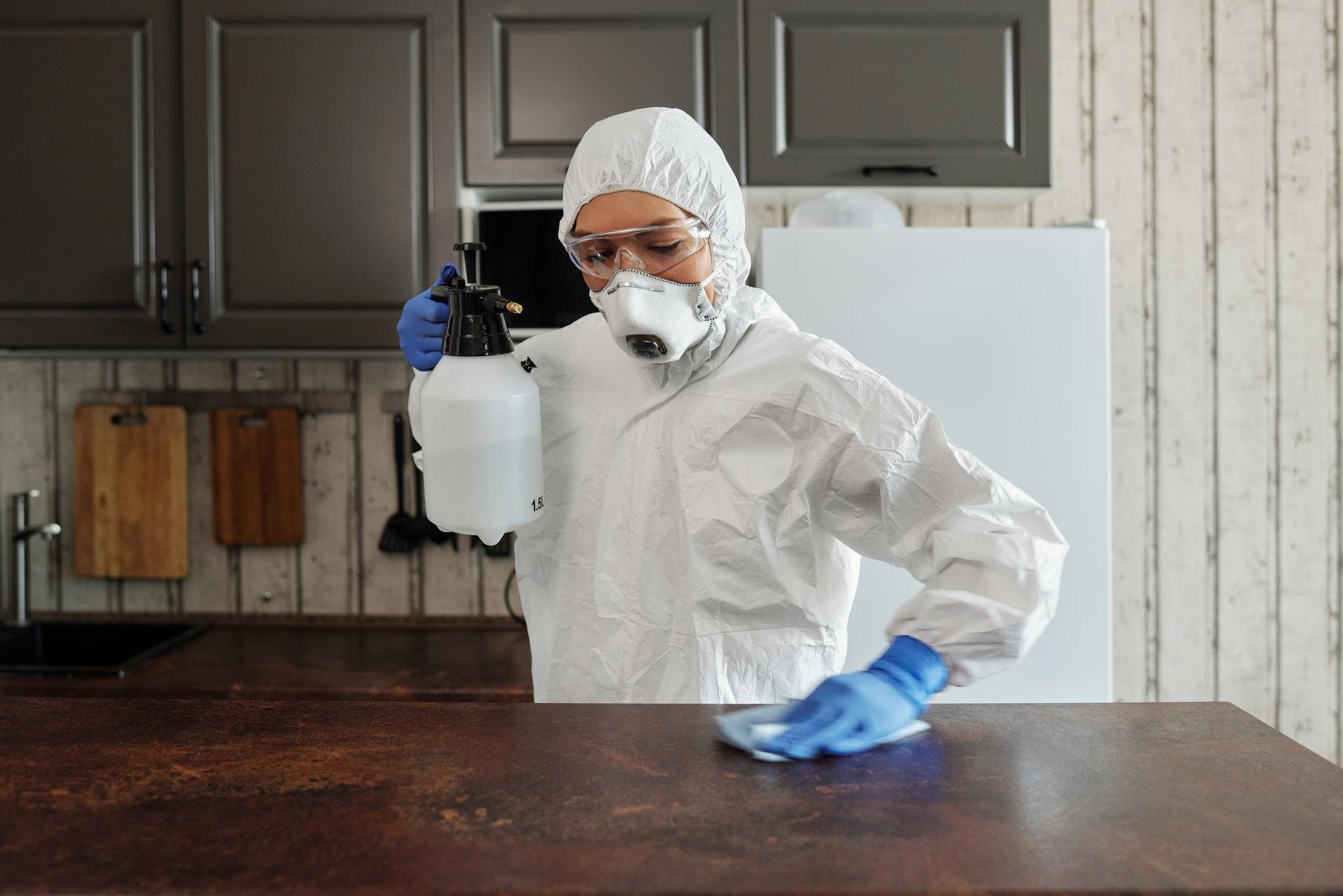 photo of person disinfecting table with liquid chemical.jpg