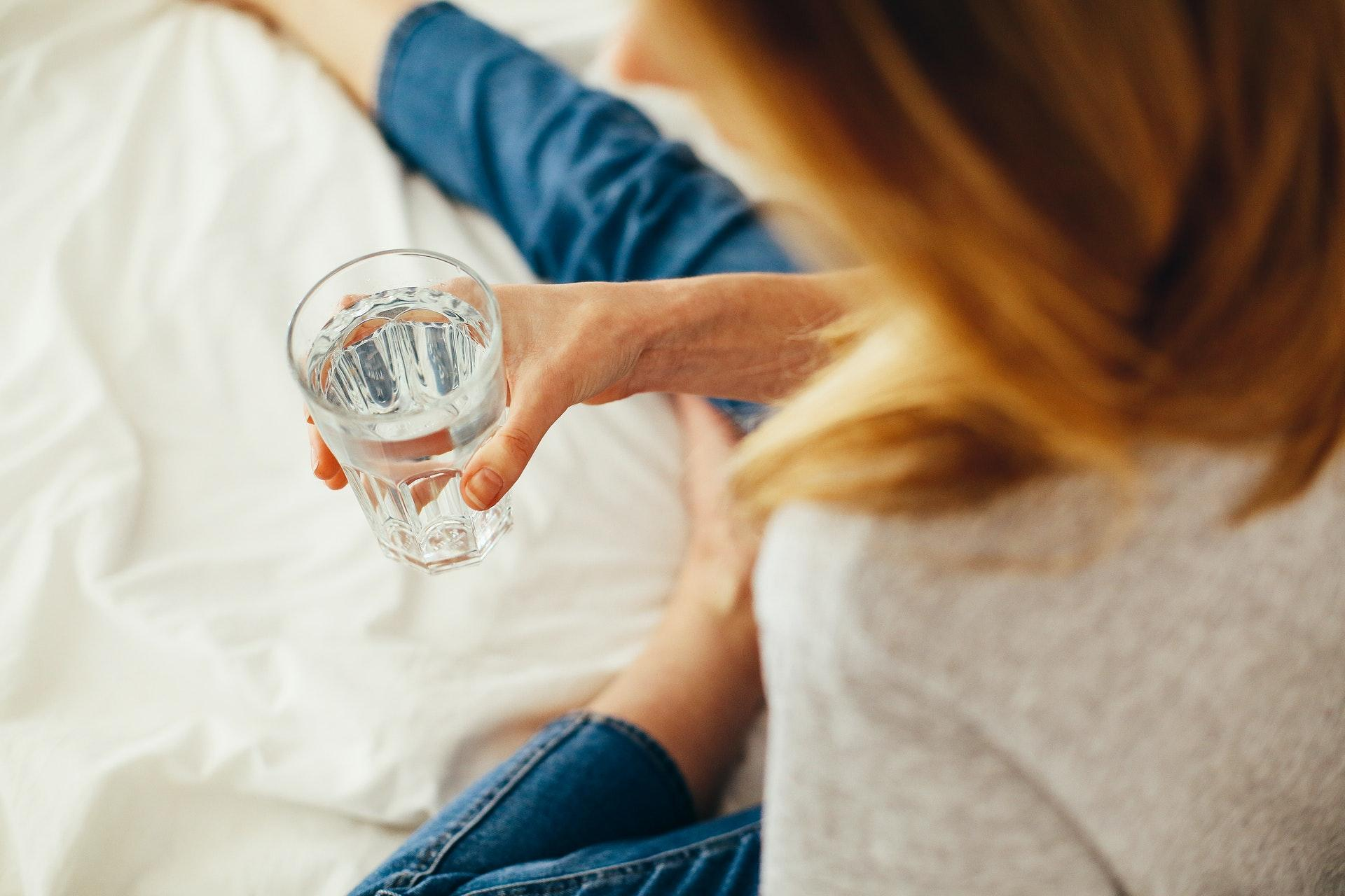 woman holding glass of water in hand laying on bed